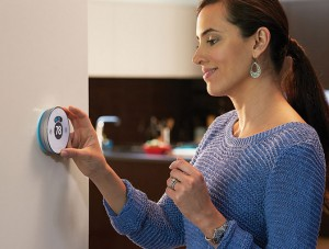 Dark haired woman turning her Wifi thermostat on the wall to the right temperature.